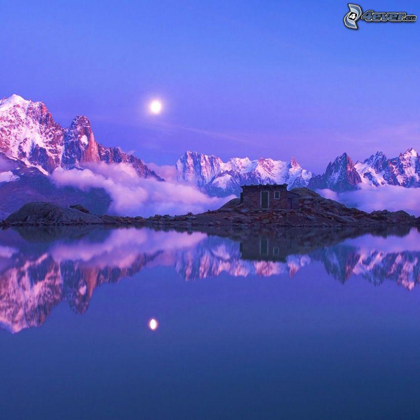 Alpy, zasnežené hory, slnko za oblakmi, domček pri jazere, odraz