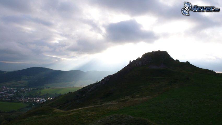 skalnatý kopec, mraky, slnečné lúče, dedinka