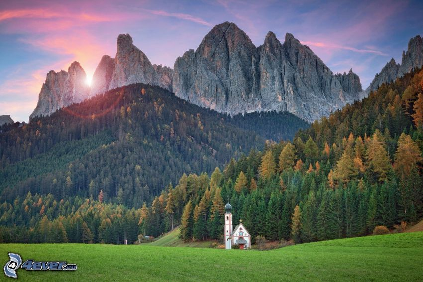 Val di Funes, kostol, ihličnatý les, skalnaté hory, západ slnka za horami, Taliansko