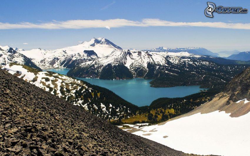 zasnežená hora nad jazerom, azúrové jazero, zasnežené kopce