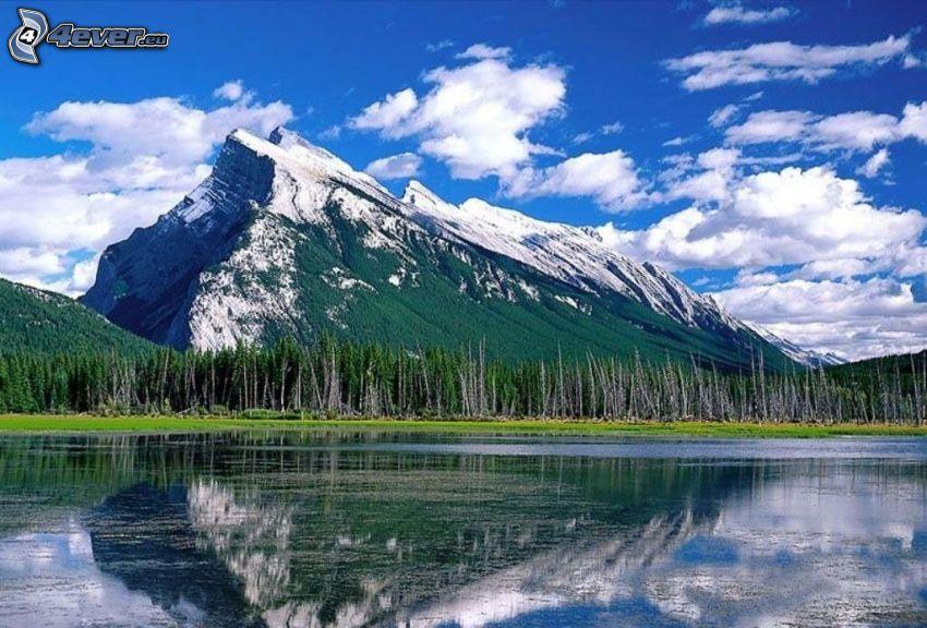 zasnežená hora nad jazerom, ihličnatý les, odraz, oblaky