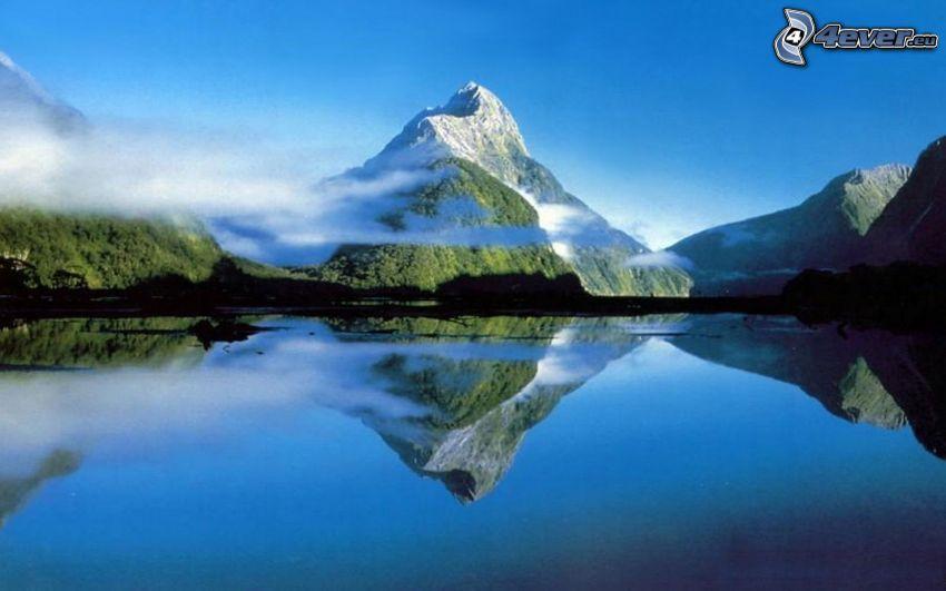 zasnežená hora nad jazerom, oblaky, pokojná vodná hladina