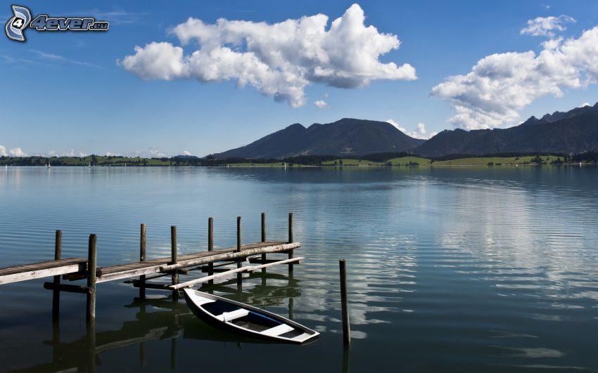 jazero, drevené mólo, čln, kopce