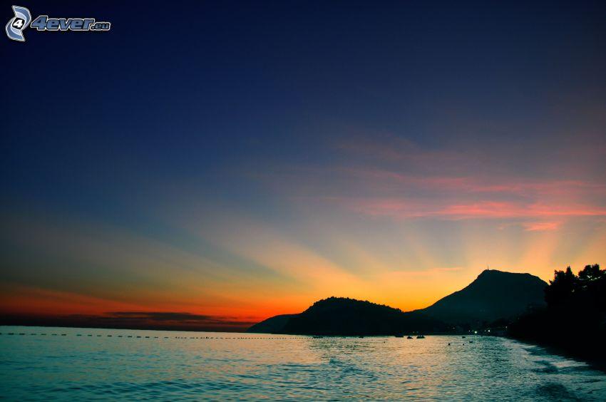 jazero, západ slnka za kopcom