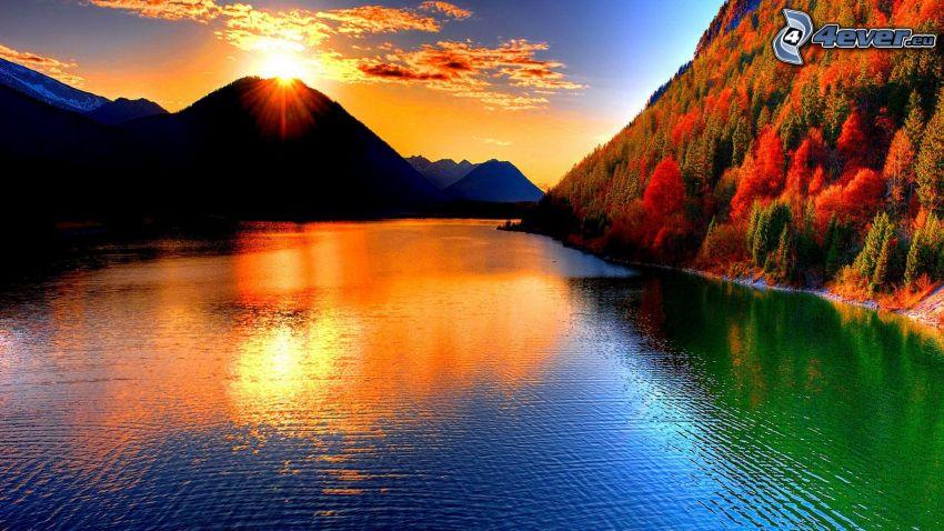 západ slnka za kopcom, farebný les, rieka