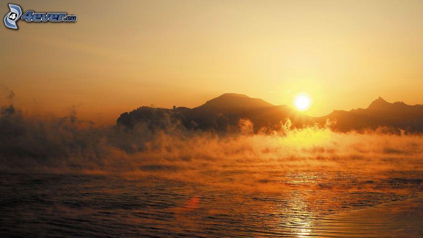 západ slnka za kopcom, jazero