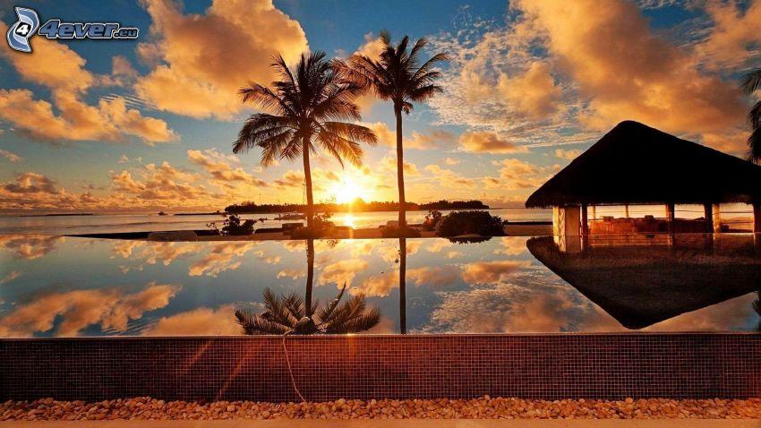 domček na vode, západ slnka za morom, palmy