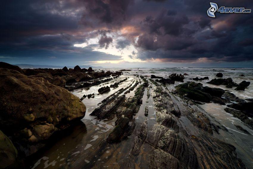kamenné pobrežie, tmavá obloha
