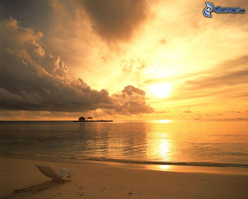 oranžový západ slnka nad morom, oblaky, lehátko, pláž, chatka, mólo