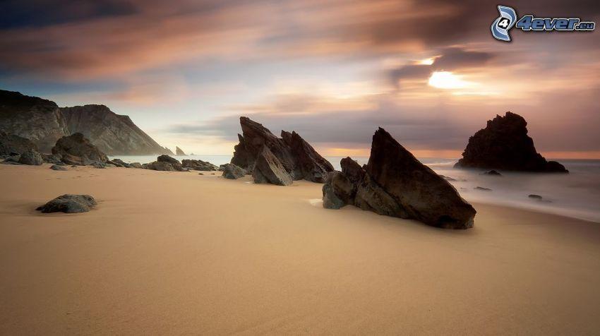 pobrežné skaly, skaly v mori, piesočná pláž, pláž po západe slnka