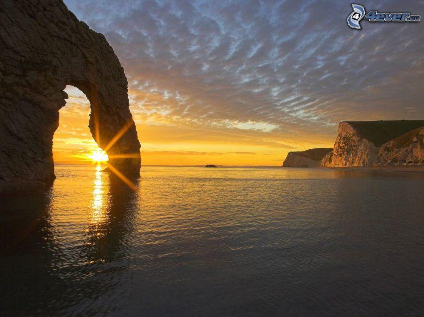 skalnatá brána na mori, západ slnka za morom