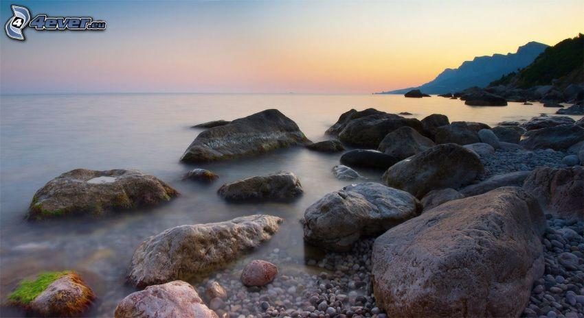 skalnaté pobrežie, skaly v mori, večerná pláž