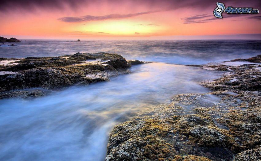 skaly v mori, ružová obloha