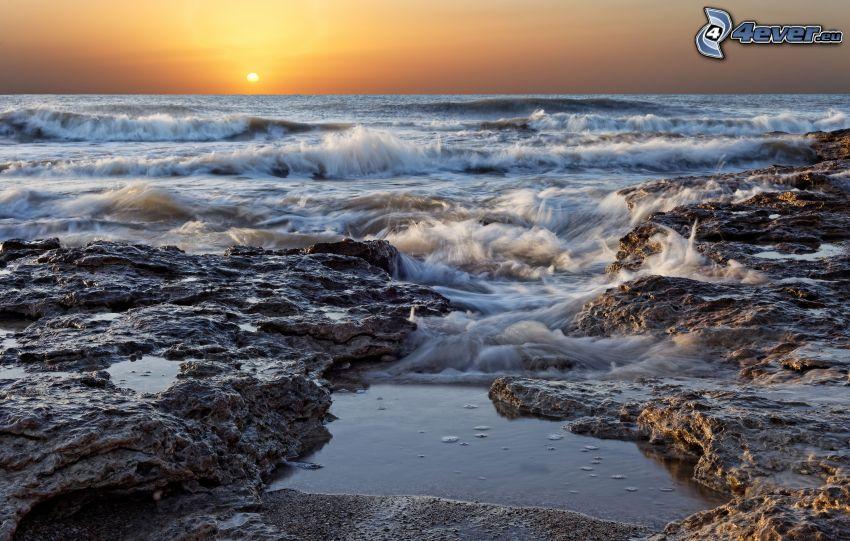 vlny na pobreží, more, skalnaté pobrežie, západ slnka za morom