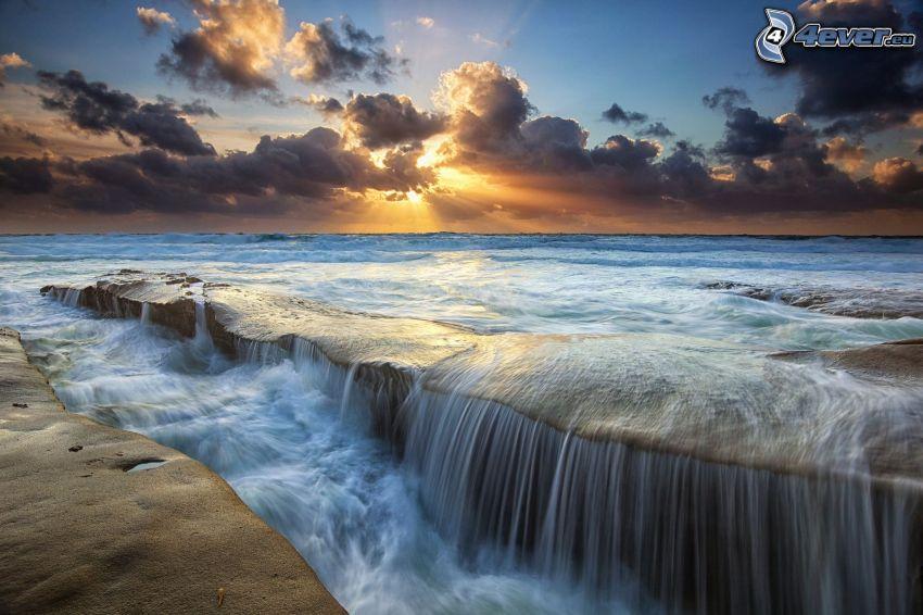 vodopády, slnečné lúče za oblakom, tmavé oblaky, západ slnka za morom