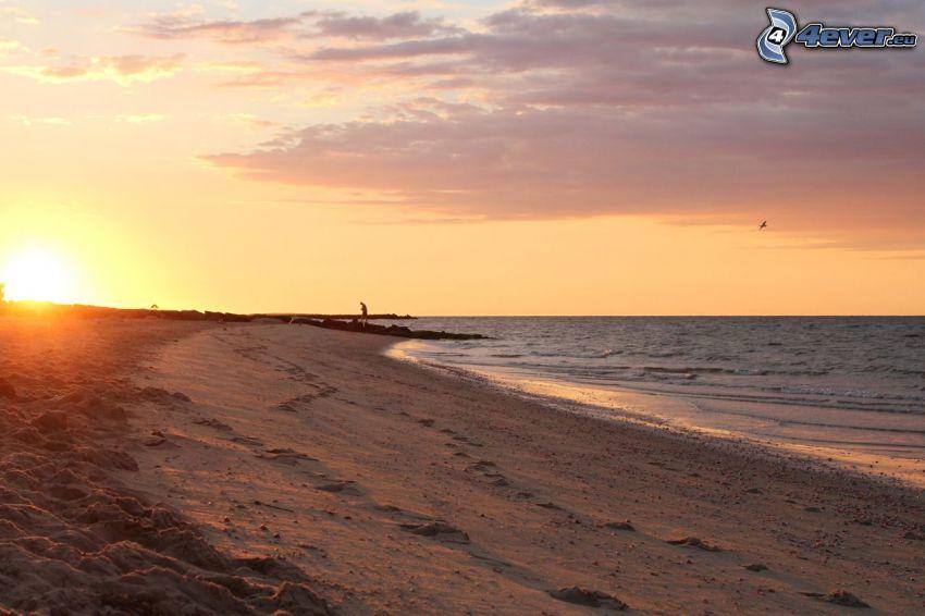 západ slnka, šíre more, piesočná pláž