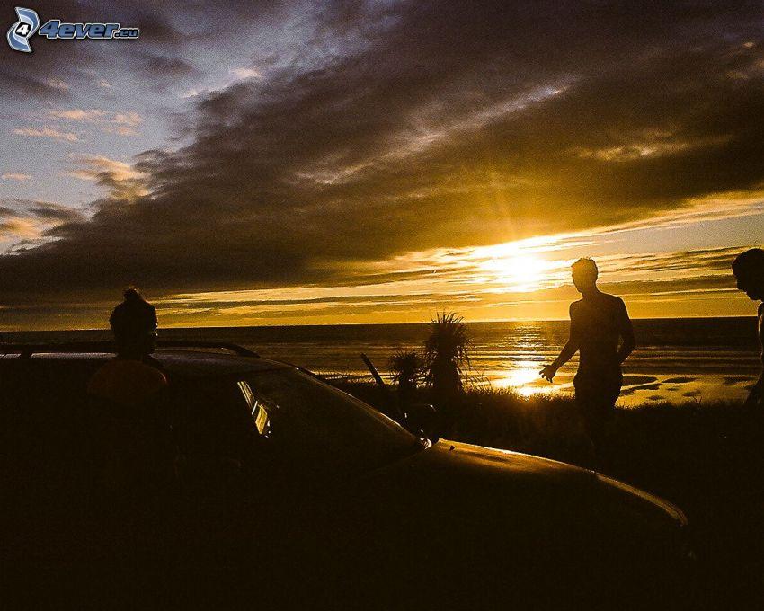 západ slnka nad morom, siluety ľudí, tmavé oblaky, šíre more