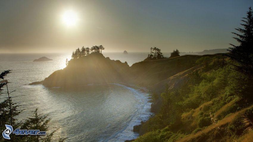 západ slnka nad morom, skalnaté pobrežie, záliv