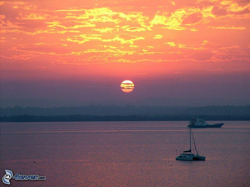 západ slnka pri mori, člny