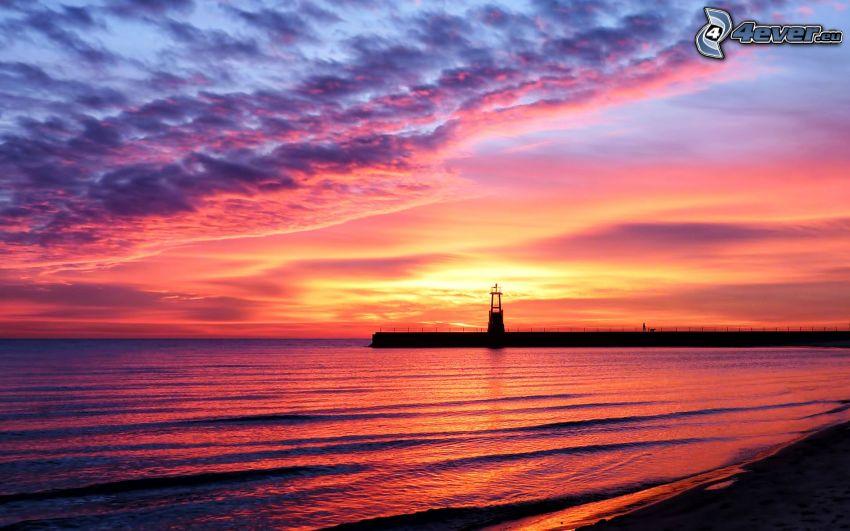 západ slnka pri mori, ružová obloha, mólo s majákom