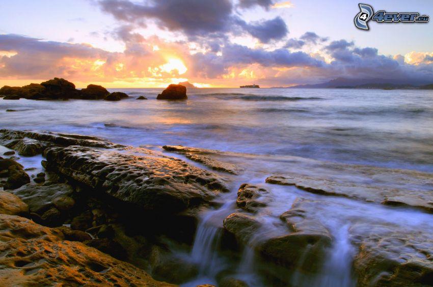 západ slnka pri mori, skaly v mori, vodopád