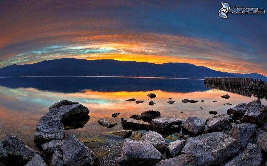 západ slnka za horami, more, skalnaté pobrežie, večerná obloha