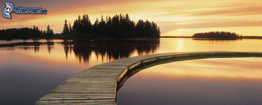 západ slnka za morom, drevené mólo, silueta lesa