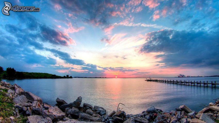 západ slnka za morom, drevené mólo, skalnatá pláž