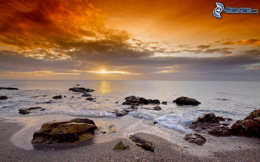 západ slnka za morom, kamenisté pobrežie