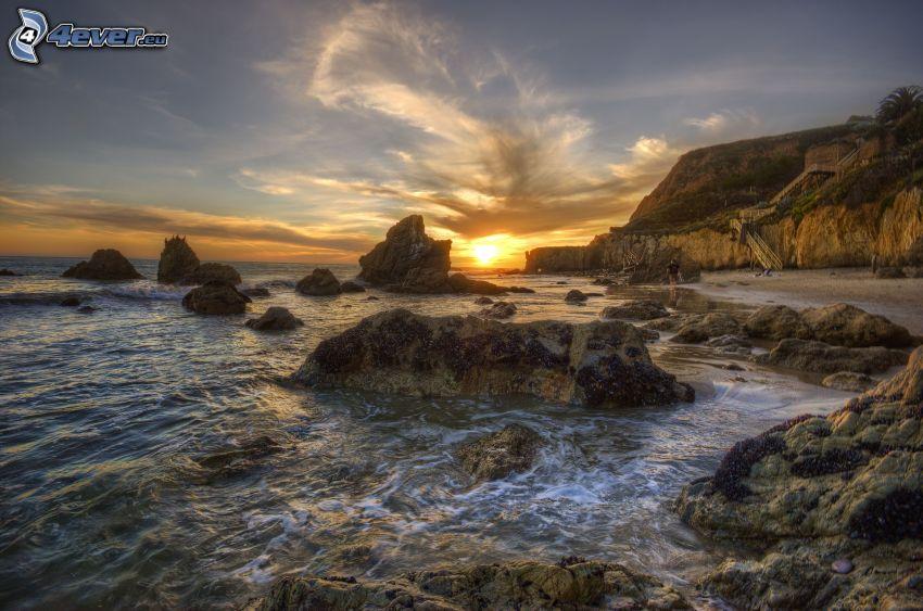 západ slnka za morom, kamenné pobrežie, HDR