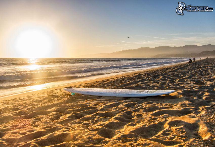 západ slnka za morom, piesočná pláž, surf