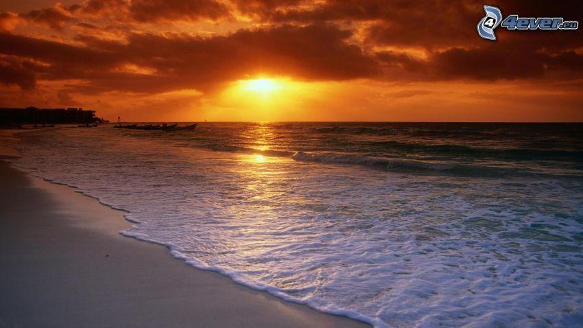 západ slnka za morom, piesočná pláž