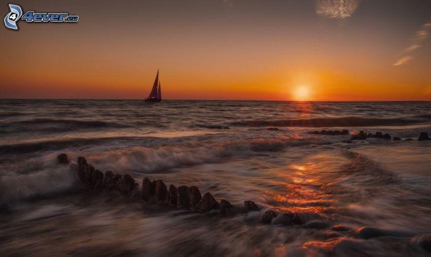 západ slnka za morom, plachetnica, skaly v mori