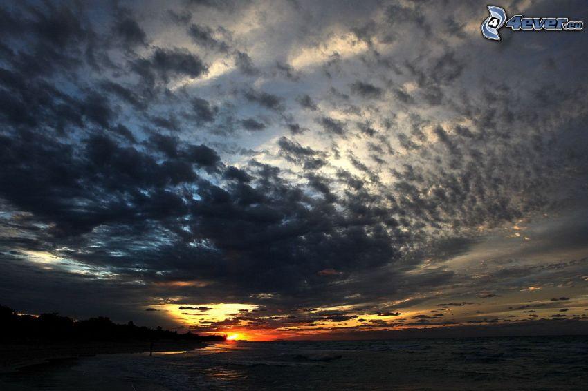 západ slnka za morom, šíre more, tmavé oblaky, pobrežie
