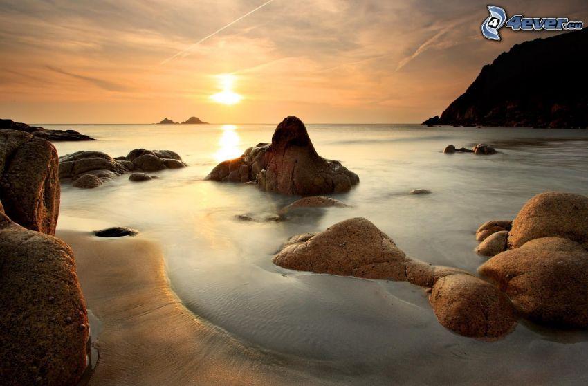 západ slnka za morom, skalnaté pobrežie