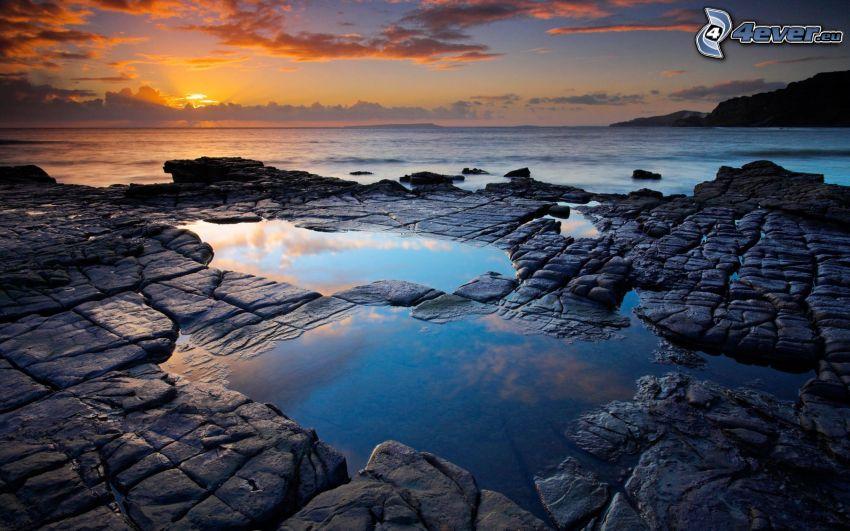 západ slnka za morom, skaly
