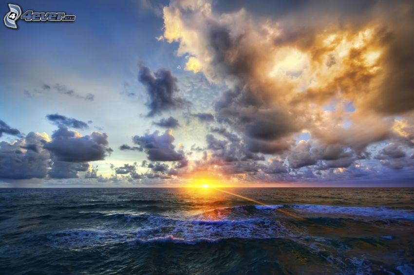 západ slnka za morom, tmavé oblaky