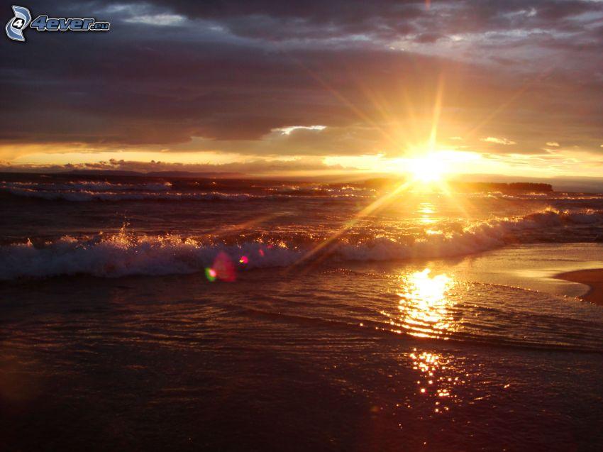 západ slnka za morom, vlny na pobreží