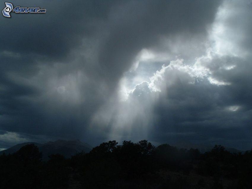tmavé oblaky, slnečné lúče, siluety stromov