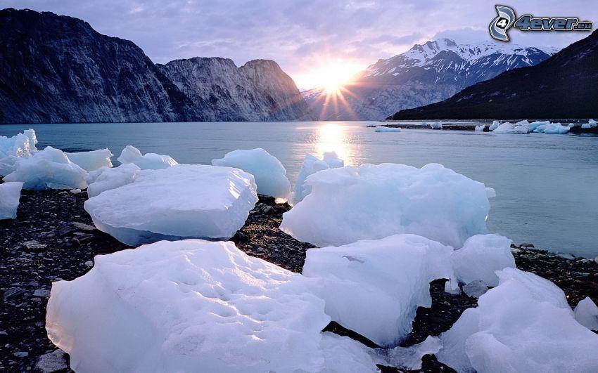 pokojné zimné jazero, ľadové kryhy, západ slnka, zasnežené hory