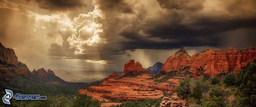 Sedona - Arizona, skaly, tmavé oblaky, slnečné lúče