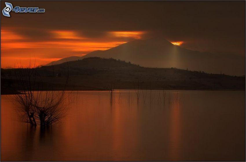 večerné pokojné jazero, západ slnka za kopcom