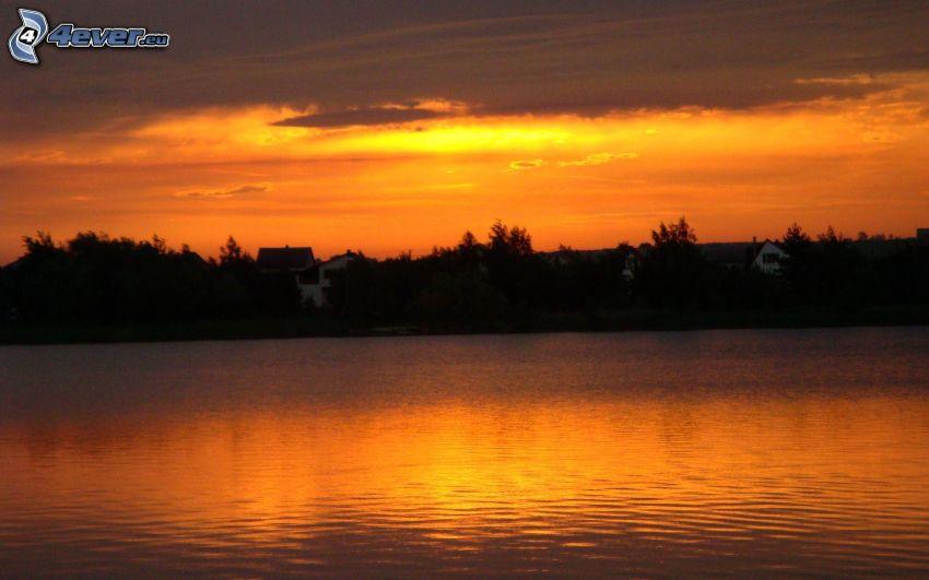 západ slnka nad jazerom, oranžová obloha