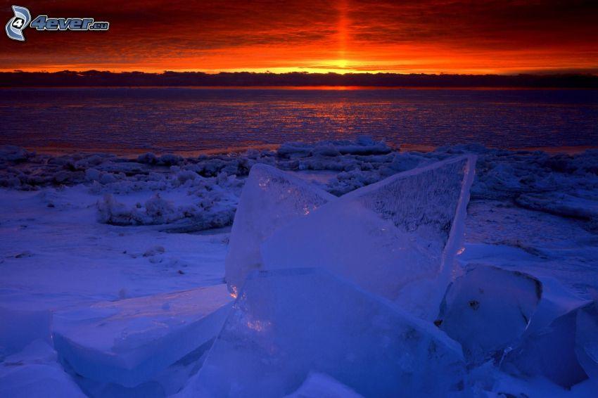 západ slnka nad riekou, ľadové kryhy, oranžová obloha