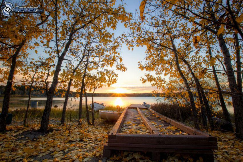 západ slnka za jazerom, mólo, člnky, jesenné stromy