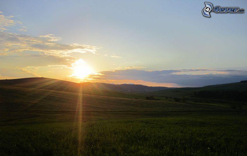 západ slnka za kopcom, lúky