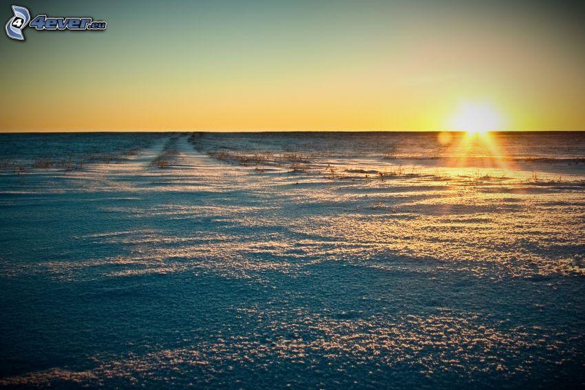 západ slnka za lúkou, zasnežená lúka