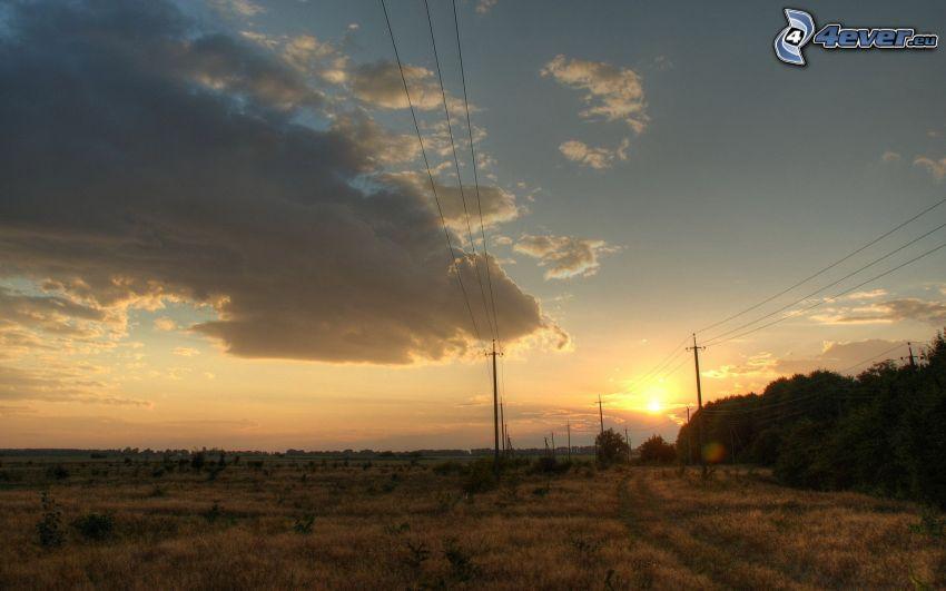 západ slnka za poľom, oblaky