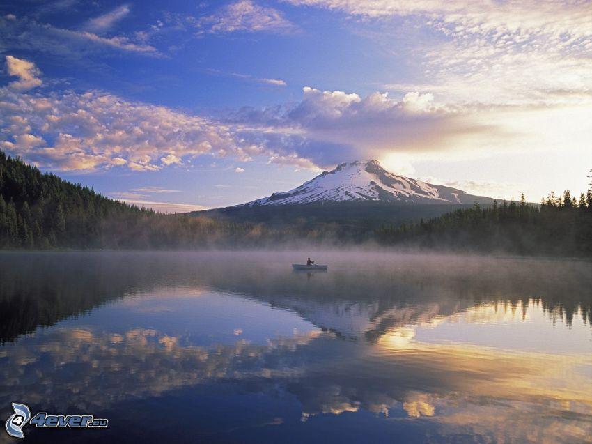 zasnežená hora nad jazerom, prízemná hmla, rybár, obloha, les, čln