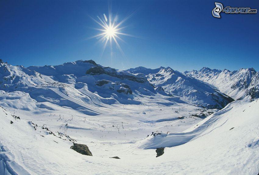zasnežené pohorie, svah, lyžiari, slnko